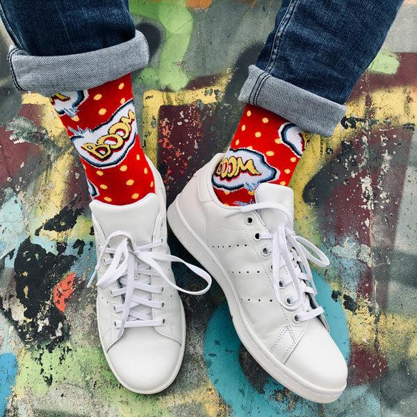 Rote lustige Socken von PATRON SOCKS mit gelben Schriftzug Boom in schwarzen Nike Schuhen